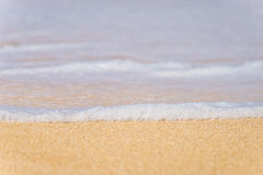 Płytka głębia pole, zbliżenie pieni się w górę brzeg woda morska Fotografia Royalty Free