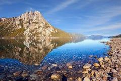 Płytki jezioro odbija ostre skały obraz stock