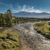 Płytki strumień w Corsica z śniegiem nakrywał góry w odległości fotografia royalty free