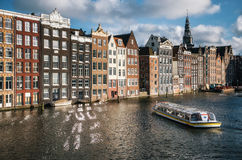 Pływa statkiem turystyczną łódź w Damrak kanale w Amsterdam przy zmierzchem Zdjęcie Stock