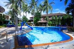 Pływacki basen, słońc loungers obok ogródu i budynki, Obrazy Royalty Free