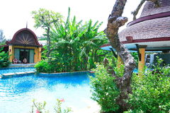 Pływacki basen, słońc loungers obok ogródu i bungalow, Obrazy Stock