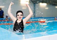 Pływackie lekcje dla dzieci w basenie - piękna jasnoskóra dziewczyna pływa w wodzie zdjęcia royalty free