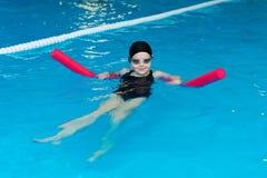 Pływackie lekcje dla dzieci w basenie - piękna jasnoskóra dziewczyna pływa w wodzie obrazy stock
