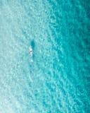 Pływaczka w błękitne wody przy wschód słońca zdjęcia stock