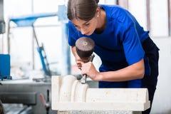 P0?:canteiro da mulher que cinzela a coluna fora da pedra na oficina fotografia de stock