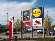 Aldi Lidl DM-drogerie and a pharmacy signpost in front of stores