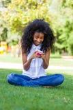 使用电话的少年黑人女孩,说谎在草-非洲p 免版税库存图片