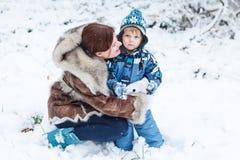 小学龄前使用与在p的第一雪的男孩和他的母亲 免版税库存图片