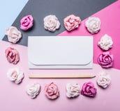 五颜六色的纸玫瑰五颜六色的背景,被折叠在情人节顶视图关闭的白色信封装饰附近p 免版税库存图片
