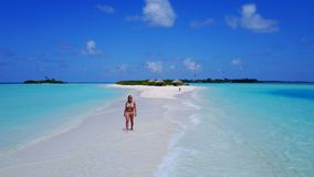 P02040 Aerial flying drone view of Maldives white sandy beach happy 1 person young beautiful young woman walking on. Aerial flying drone view of Maldives white royalty free stock images