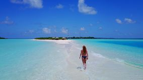 P02065 Aerial flying drone view of Maldives white sandy beach happy 1 person young beautiful young woman walking on. Aerial flying drone view of Maldives white stock images
