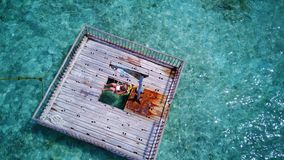 P02009 Aerial flying drone view of Maldives white sandy beach happy young woman relaxing on floating pontoon jetty Stock Photos