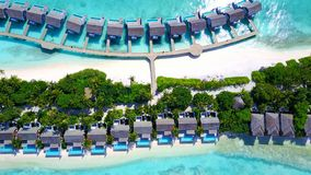P00135 Aerial flying drone view of Maldives white sandy beach luxury 5 star resort hotel water bungalows relaxing holiday vacation Stock Photos
