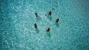 P02138 Aerial flying drone view of Maldives white sandy beach 5 people young woman playing ball fun together on sunny royalty free stock images