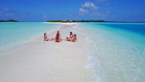 P02151 Aerial flying drone view of Maldives white sandy beach 5 people young woman relaxing sunbathing together on sunny Stock Image