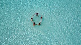 P02178 Aerial flying drone view of Maldives white sandy beach 5 people young woman relaxing sunbathing together on sunny Stock Photography