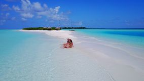 P02160 Aerial flying drone view of Maldives white sandy beach 5 people young woman relaxing sunbathing together on sunny Stock Image