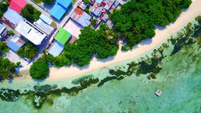 P01207 Aerial flying drone view of Maldives white sandy beach on sunny tropical paradise island with aqua blue sky sea Royalty Free Stock Image