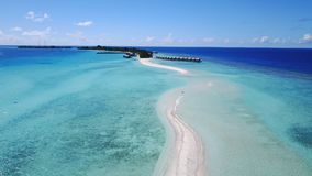 P01025 Aerial flying drone view of Maldives white sandy beach on sunny tropical paradise island with aqua blue sky sea Stock Photo