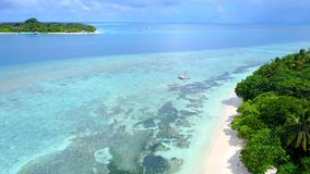 P02275 Aerial flying drone view of Maldives white sandy beach on sunny tropical paradise island with aqua blue sky sea Stock Photos