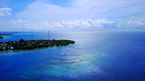 P02278 Aerial flying drone view of Maldives white sandy beach on sunny tropical paradise island with aqua blue sky sea Stock Images