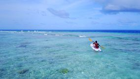 P02069 Aerial flying drone view of Maldives white sandy beach young man relaxing on paddleboard on sunny tropical. Aerial flying drone view of Maldives white Royalty Free Stock Images
