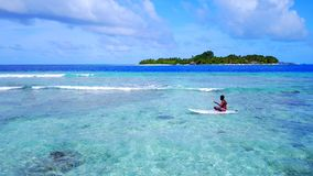 P02071 Aerial flying drone view of Maldives white sandy beach young man relaxing on paddleboard on sunny tropical. Aerial flying drone view of Maldives white Royalty Free Stock Photo
