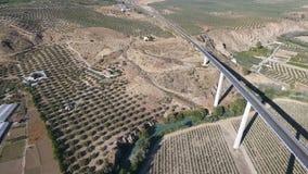 1080p antena, lot nad rzeczną wioską i oliwnymi sadami autostrada puszka i mosta, Andalucia, Hiszpania Staright rzędy oliwny tre zbiory