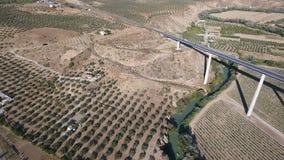 1080p antenna, volo sopra un villaggio del fiume giù e del ponte stradale ed i frutteti dell'oliva, Andalusia, Spagna File di Sta video d archivio