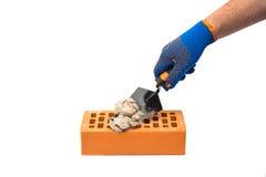 Pá de pedreiro da construção na mão masculina com luvas da construção Imagens de Stock Royalty Free