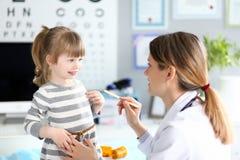 P?diatre f?minin examinant peu de gorge patiente d'enfant avec le b?ton en bois images libres de droits