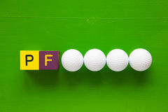 P.F. - an inscription from children's wooden blocks and golf bal Stock Photography