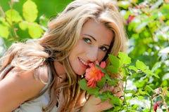 P-Frau, die eine Rose riecht Stockfotografie