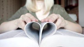 P?ginas rubias irreconocibles borrosas en una forma del coraz?n, concepto de lectura del libro de plegamiento de la mujer del amo almacen de metraje de vídeo