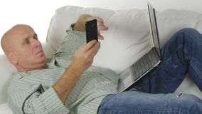 Relaxed Man Resting in the Couch Text Using Smartphone royalty free stock images