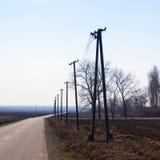 Pôles de téléphone par la route Photo stock