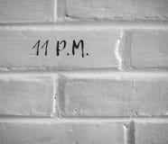 11 p M НАПИСАННЫЙ НА БЕЛОЙ ПРОСТОЙ КИРПИЧНОЙ СТЕНЕ Стоковое Изображение RF