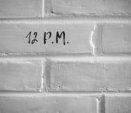 12 P.M. WRITTEN ON WHITE PLAIN BRICK WALL Royalty Free Stock Photos