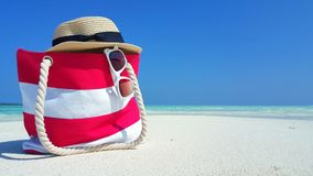 P00150 Maldives white sandy beach bag hat sunglasses and flipflops on sunny tropical paradise island with aqua blue sky. Maldives white sandy beach bag hat Royalty Free Stock Photos