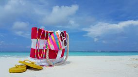 P00161 Maldives white sandy beach bag sunglasses bikini on sunny tropical paradise island with aqua blue sky sea ocean 4k Royalty Free Stock Photography