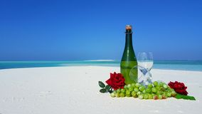 P02874 Maldives white sandy beach champagne bottle and glasses on sunny tropical paradise island with aqua blue sky sea Royalty Free Stock Images