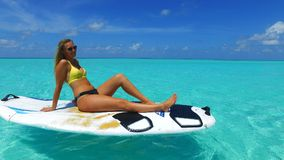 P02817 Maldives white sandy beach 1 people a young beautiful woman sitting relaxing on paddle board on sunny tropical. Maldives white sandy beach 1 people a Royalty Free Stock Photo