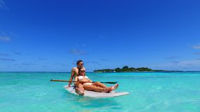 P02925 Maldives white sandy beach 2 people young couple man woman paddleboard rowing on sunny tropical paradise island Stock Image