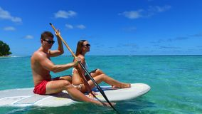 P02926 Maldives white sandy beach 2 people young couple man woman paddleboard rowing on sunny tropical paradise island Royalty Free Stock Photography