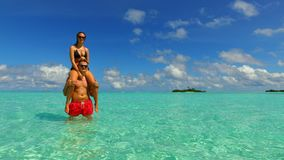 P02958 Maldives white sandy beach 2 people a young couple man woman romantic love on sunny tropical paradise island with Stock Image