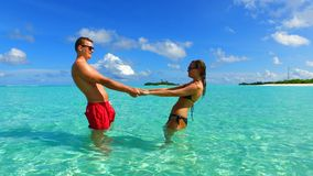 P02944 Maldives white sandy beach 2 people a young couple man woman romantic love on sunny tropical paradise island with Stock Photography