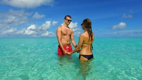 P02950 Maldives white sandy beach 2 people a young couple man woman romantic love on sunny tropical paradise island with Stock Photo