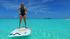 P02824 Maldives white sandy beach 1 people a young woman standing on paddle board on sunny tropical paradise island with Stock Photography