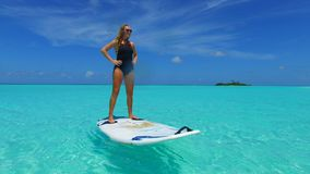 P02825 Maldives white sandy beach 1 people a young woman standing on paddle board on sunny tropical paradise island with Stock Photo